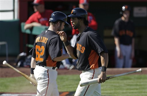 San Francisco Giants' Angel Pagan, right, is congratulated by Jackson Williams after Pagan scored during the fourth inning of an exhibition spring training baseball game against the Los Angeles Angels Saturday, Feb. 23, 2013, in Scottsdale, Ariz. (AP Photo/Darron Cummings)