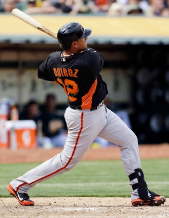 San Francisco Giants' Guillermo Quiroz hits a three-run home run off Oakland Athletics pitcher Bartolo Colon during the seventh inning of a baseball game on Saturday, March 30, 2013, in Oakland, Calif. Oakland won the game 4-3. (AP Photo/Eric Risberg)