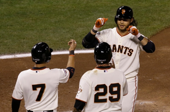 San Francisco Giants' Brandon Crawford, top, is congratulated after hitting a three-run home run off of Colorado Rockies pitcher Adam Ottavino to score Gregor Blanco (7) and Hector Sanchez (29) during the sixth inning of a baseball game in San Francisco, Tuesday, April 9, 2013. (AP Photo/Jeff Chiu)