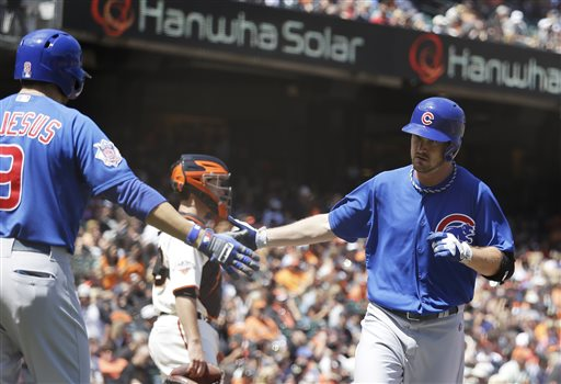 Chicago Cubs' Travis Wood, right, is greeted by teammate David DeJesus, left, after hitting a home run off San Francisco Giants starting pitcher Tim Lincecum during the fifth inning of their baseball game on Sunday, July 28, 2013, in San Francisco. Giants catcher Buster Posey, center, looks on. (AP Photo/Eric Risberg)
