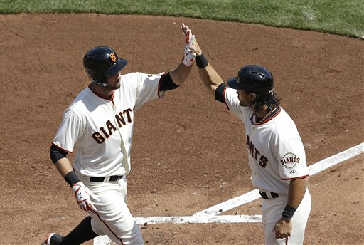 San Francisco Giants' Brandon Belt, left, is congratulated by Angel Pagan after hitting a two-run home run off of Arizona Diamondbacks pitcher Trevor Cahill that scored Pagan during the first inning of an opening day baseball game in San Francisco, Tuesday, April 8, 2014. (AP Photo/Jeff Chiu)