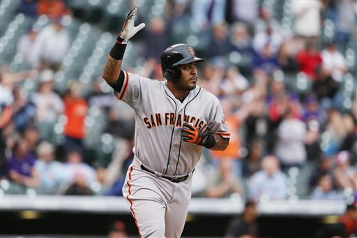 San Francisco Giants' Hector Sanchez celebrates his grand slam against the Colorado Rockies as he circles the bases in the 11th inning of the Giants' 12-10 victory in 11 innings of a baseball game in Denver on Wednesday, April 23, 2014. (AP Photo/David Zalubowski)